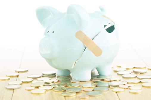 Coins spilled from broken piggy bank